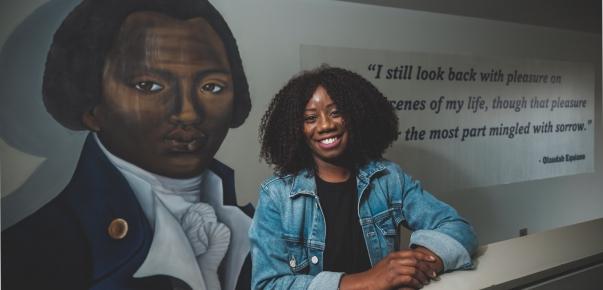 Artist stood next to portrait mural of man